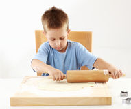 Small boy rolling dough for cookies Royalty Free Stock Photos