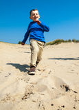 Small boy running down sand dune Royalty Free Stock Image