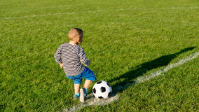 Small boy running with a soccer ball Stock Images