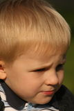 Small boy's face in the sunshine. Small boy sitting on the bench and watching water Royalty Free Stock Images