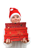 Small boy in Santa red hat carrying three presents Stock Photo