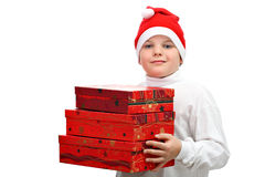 Small boy in Santa red hat carrying three presents Royalty Free Stock Photos