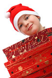 Small boy in Santa red hat carrying three presents Royalty Free Stock Images