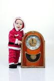 Small boy in Santa suit plays with vintage clock in white studio Stock Photos