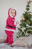 Small boy in Santa suit plays in white studio Stock Images