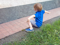 Small boy sat on garden wall, arms outstretched. Playing outside Stock Images