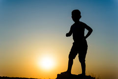 Small boy silhouetted by a colorful sunset Royalty Free Stock Images