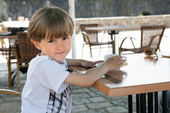 The small boy sits in cafe Royalty Free Stock Photo