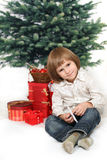 Small boy sits with christmas presents Royalty Free Stock Photos