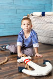 Small boy sits and holds the armature Royalty Free Stock Image