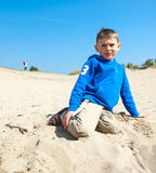 Small boy sitting at the base of a sand dune Stock Images