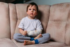 A small boy is sitting on a chair with a broken arm, in a cast. hospital. medicine. danger. pain. to break limbs. violence. stock photography