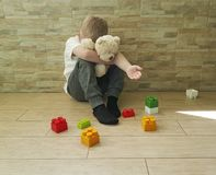 Small sad boy sitting on the floor  expression tenderness unhappy a block depression frustratedsadness. Small boy sitting on the floor with a block unhappy Royalty Free Stock Photo