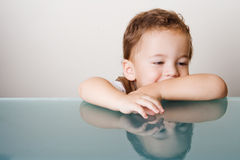Small boy sitting at glass table Royalty Free Stock Photos