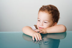 Small boy sitting by glass table Royalty Free Stock Images