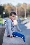 Small boy sitting on granite  and looking at camera Royalty Free Stock Images