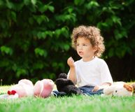 Small boy sitting on grass Stock Photos