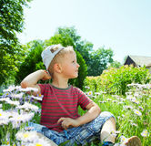 Small boy sitting on the grass Royalty Free Stock Photography
