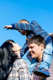 Small boy is sitting on his father`s shoulders. And mother against the background of the blue sky Royalty Free Stock Photos
