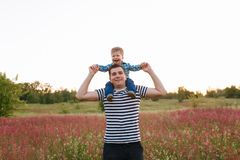 Small boy sitting on his fathers shoulders and holding hands in the field during beautiful sunset.  stock image