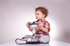Small boy sitting and holding a trophy. Portrait of a small boy holding a trophy and looking away from the camera. Gray background Stock Images