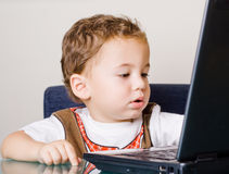 Small boy sitting by the laptop Royalty Free Stock Photos