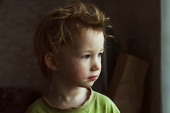 Small boy sitting near window and thinking about something. He has beautiful great hair. Cute baby. Small littke boy sitting near window and thinking about Stock Photos