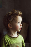 Small boy sitting near window and thinking about something. He has beautiful great hair. Cute baby. Small littke boy sitting near window and thinking about Royalty Free Stock Photography