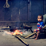 Small boy sitting by open fire  Stock Photo