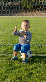 Small boy sitting on soccer ball Royalty Free Stock Photography