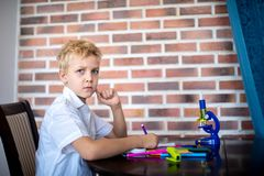 Small boy is sitting at table stock photography