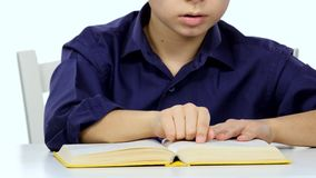 Small boy sitting at a table and reads interesting book slowly. White background. Close up stock video footage