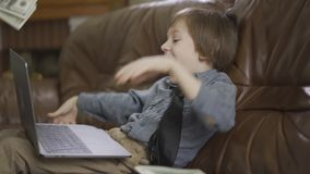Portrait adorable small boy sitting on the leather sofa with laptop computer on the legs and throwing money in the air stock footage
