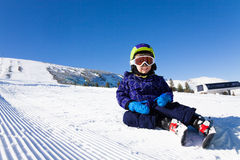 Small boy in ski mask sitting on the snow Royalty Free Stock Photos