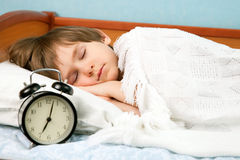 The small boy sleeps. In bed with wake-up clock Stock Images