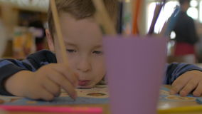 Small boy solves kids exercise in developing book for preschool children unfocused glass with pencils on the foreground. Small concentrated boy solves kids stock footage