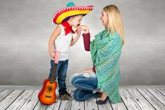 A small boy in a sombrero kisses mom`s hand. Son plays the guitar and sings a serenade for his mother Stock Photo