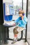 Small boy speaks by public pay telephone Stock Photos