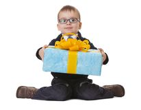 Small boy in spectecles with big present. Small sitting boy in spectacles holds a big blue present on white background Royalty Free Stock Photography