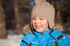 Small boy squinted at sun, winter, park Royalty Free Stock Photos