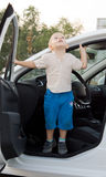Small boy standing in a car door Royalty Free Stock Photos