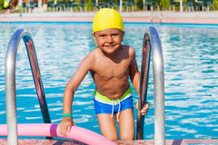 Small boy standing with pool noodle holding ladder Royalty Free Stock Photos