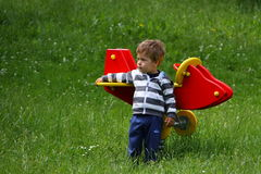 Small boy standing by the red airplane swing in high grass Royalty Free Stock Photography