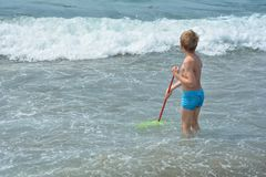 113ba72763 Small boy stands with a fishing-net in the water royalty free stock photo