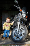 Small boy stands near big motorcycle Stock Image