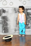 Small boy stands near the gray wall Royalty Free Stock Photography