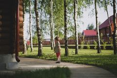 A small boy stands next to a wooden country house surrounded by trees. royalty free stock photography