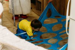 A small boy steps over, climbs, rails, passes into a hole, a cut, an opening in a blue fabric, in matter. child Game. tunnel, laby. Rinth. child playing the game stock image