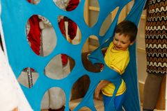 A small boy steps over, climbs, rails, passes into a hole, a cut, an opening in a blue fabric, in matter. child Game. tunnel, laby. Rinth. child playing the game stock photos