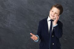 Small boy in suit talking on mobile phone. Pretending to be businessman. Small boy in suit taking on mobile phone and gesticulating, studio background, copy royalty free stock photography